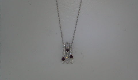 Ruby pendant in 14kt white gold with 3 rubies =.27ct and 22 diamonds =.32ct on an 18in chain.  Style 723-0024 $1495.00