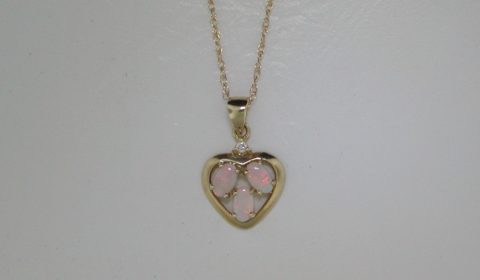 Crystal opal heart shaped pendant in 14kt yellow gold with 1 diamond =.02ct on an 18in chain.  Style 801-0003.  $795.00.